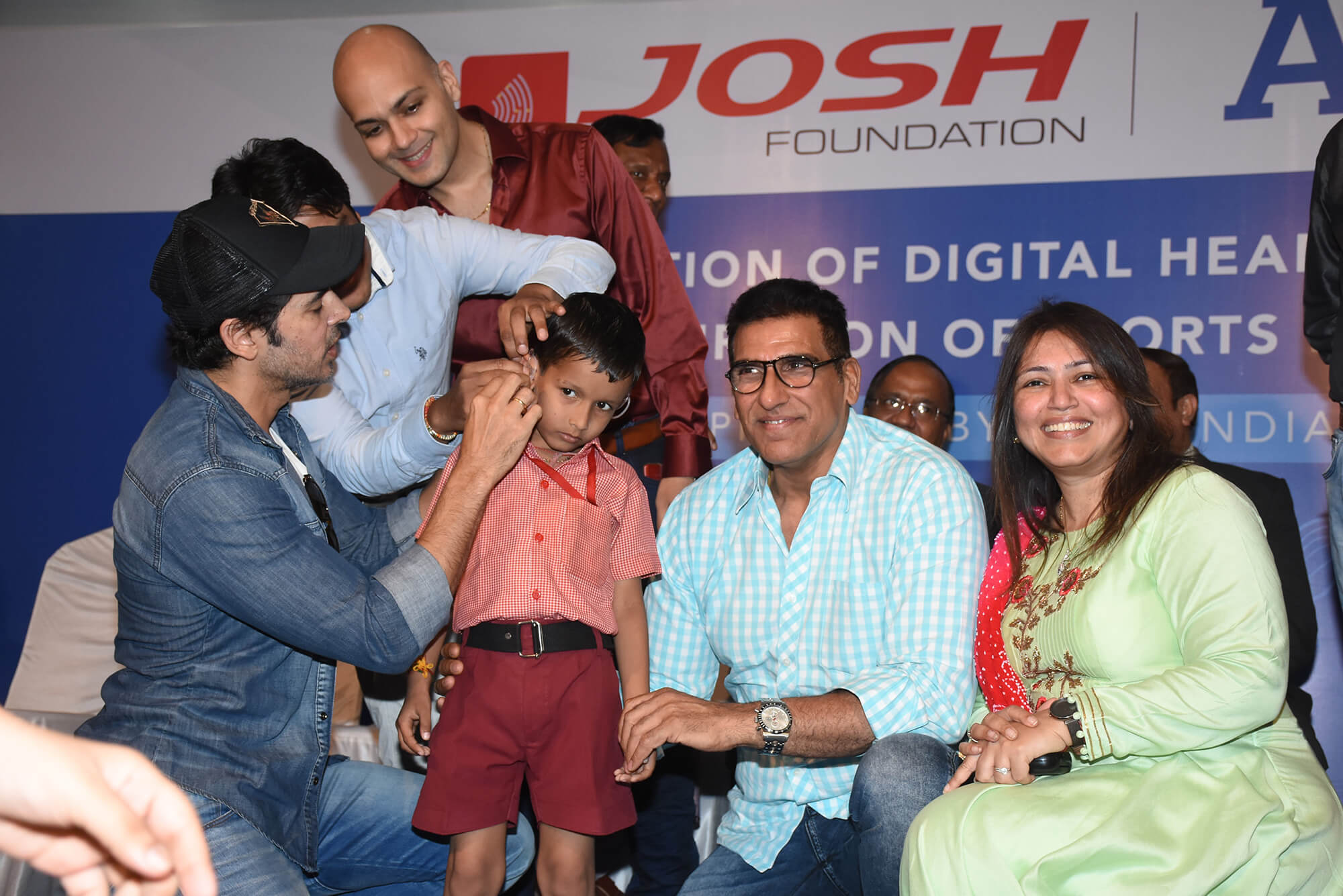Dino-Morea-helps-fit-a-hearing-aid-to-a-kid-as-Dr.Farhad-Vijay-Arora-Mukesh-Rishi-and-Devangi-Dalal-watch-on-at-the-JOSH-Foundation-ATOS-free-digital-hearing-aid-distribution-initiative